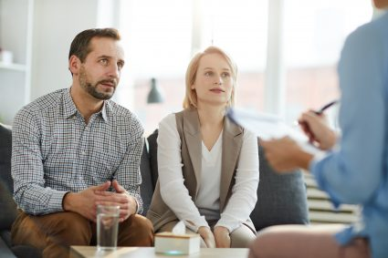 Young couple sitting on couch in front of psychologist and listening to her advice at meeting