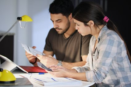 Young couple reviewing invoices and doing family business plan. Concept of money and economic problem for man and woman living together